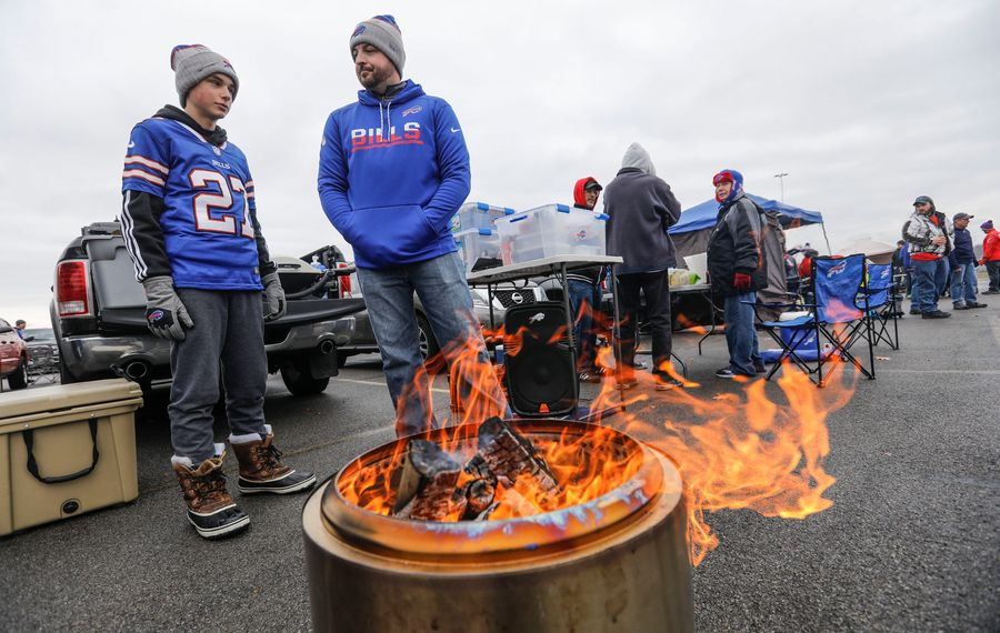 Eric Brooks and his son Caleb, 14, of East Bethany warm up by the fire before the Bills game against Jacksonville in the parking lot outside New Era Field in Orchard Park, Sunday, Nov. 25, 2018. (Derek Gee/Buffalo News)