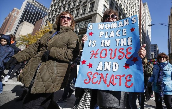 "A woman holds a sign during a rally on Oct. 13 in Chicago to inspire voter turnout ahead of the midterm elections. Many women are angered by the bitter fight over a U.S. Supreme Court nominee and what they call the ""anti-woman agenda"" of the Trump administration. (Getty Images)"