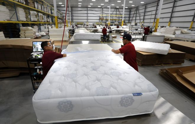 Enoc Soto, left, and Isaiah Divers cover a finished mattress in plastic at the City Mattress facility in Depew. (Mark Mulville/Buffalo News)