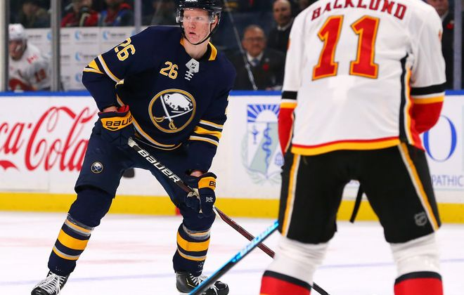 Rasmus Dahlin works the puck against Calgary's Mikael Backlund during the Sabres' failed overtime power play against the Flames on Oct. 30 in KeyBank Center. (Getty Images)