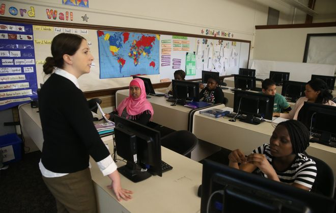 Alyssa Van Wormer, left,  works with students in a 9th grade English as a second language class at the Newcomer Academy @ Lafayette High School.  (John Hickey/Buffalo News file photo)