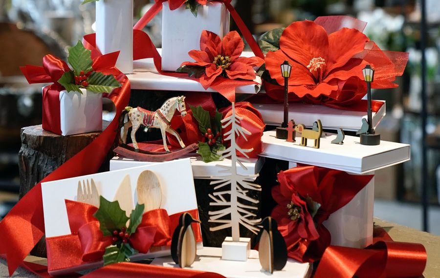 Neo offers free wrapping—white with red ribbon, topped with a poinsettia—and special packaging for purchase, like the three-dimensional boxes above designed to house gift cards. (Dave Jarosz)