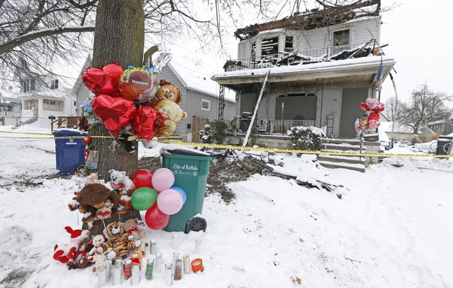 The tree in front of the Benzinger Street home where a fatal fire occurred is decorated with items as a memorial. (Robert Kirkham/Buffalo News)