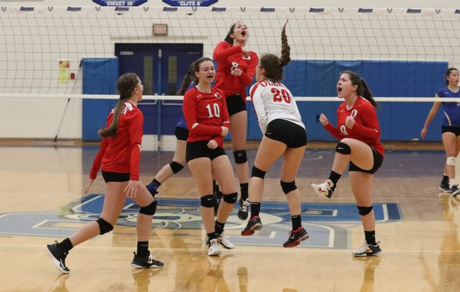 Olean players celebrate a point win in the Class B girls volleyball crossover. (James P. McCoy/Buffalo News)