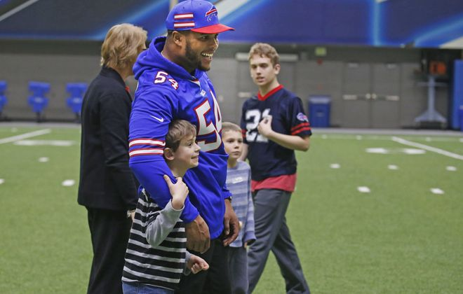 The Buffalo Bills' Eddie Yarbrough takes Dylan Swanson, 9, of Orchard Park into a hug in the ADPRO Buffalo Bills practice fieldhouse on Monday, Nov. 26, 2018.  (Robert Kirkham/Buffalo News)