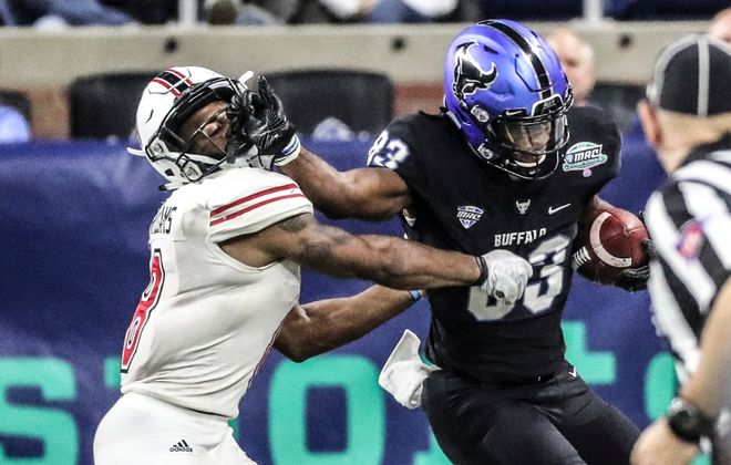 Bulls wide receiver Anthony Johnson stiff-arms Northern Illinois' Rodney Hall on the way to a first down. (James P. McCoy/Buffalo News)