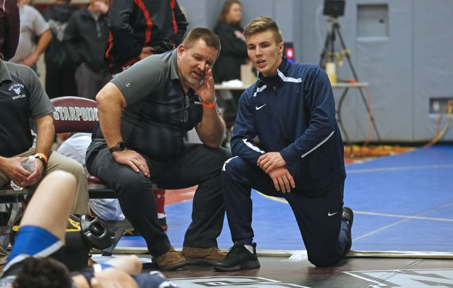 East Aurora senior wrestler Johhny Putney, left, discusses strategy with coach Jeff Michel during the ECIC championships on Friday at Starpoint. (Robert Kirkham/Buffalo News)