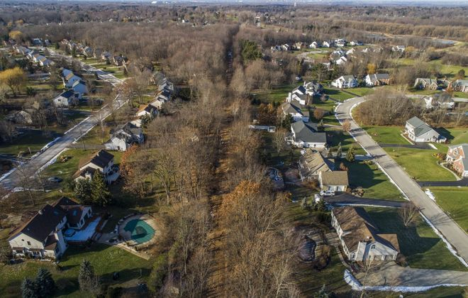 A former rail bed that runs between two neighborhoods in Orchard Park is planned for a Rails to Trails conversion. Some  residents on Curley Drive, left, and Deer Run, right, are opposed to the plan. (Derek Gee/Buffalo News)