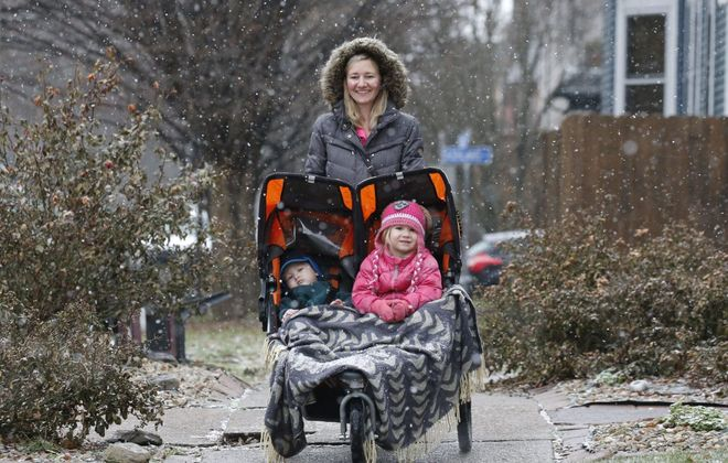 Bonnie Lorentz takes a walk with her son Leo, 1, and daughter Violet, 3, to enjoy the falling snow in the Elmwood Village on Dec. 24, 2018.   (Derek Gee/Buffalo News)