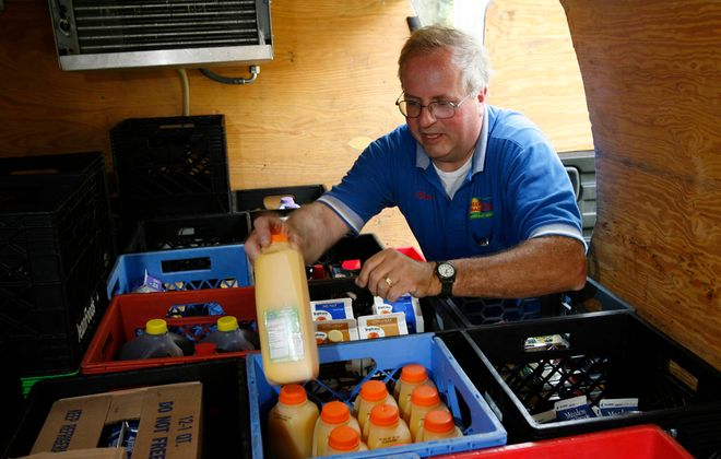 Bradley Hellert, owner of Hillside Dairy, was the only person in Erie County still delivering bottles of milk. He is retiring at the end of the year.  Here, Hellert is at his refrigerated van filling an order.  Customers usually leave a note with their order on the door or in the milk box  on Thursday,  May 31, 2007.  (Sharon Cantillon on Thursday)