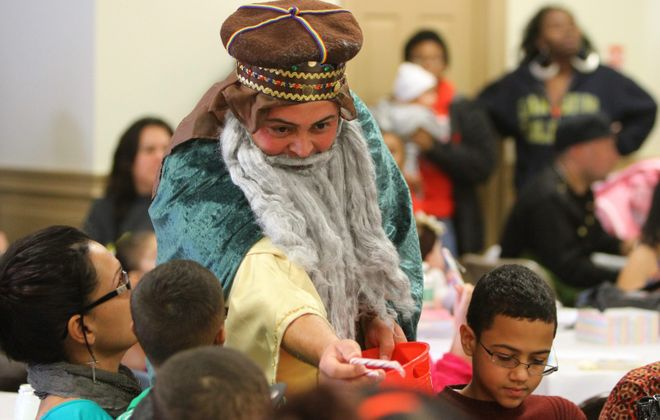 Rudy Torres hands out candy canes to children during the annual Three Kings Day celebration at the Olivencia Center in 2014.  (Mark Mulville/News file photo)
