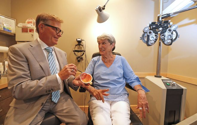 Dr. Paul Holmwood, an ophthalmologist, and one of his patients, Betty Fecteau, of West Seneca, talk about Fecteau's glaucoma treatments last year.  (Robert Kirkham/News file photo)