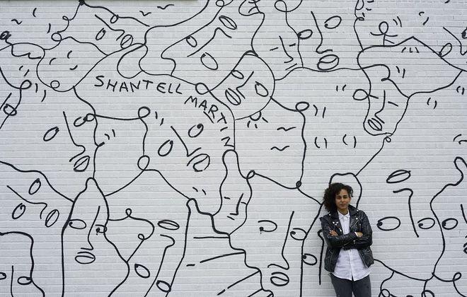 "Artist Shantell Martin, of London, poses in front of her mural, ""Dance Everyday,"" on East Delavan. (Derek Gee/Buffalo News)"