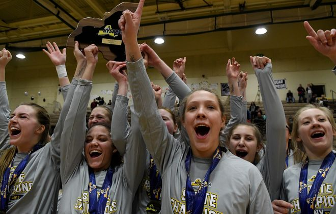 Franklinville girls basketball players cheer and hold the New York state championship for their supporters to see following their victory. (Jenn March / Special to the Buffalo News)