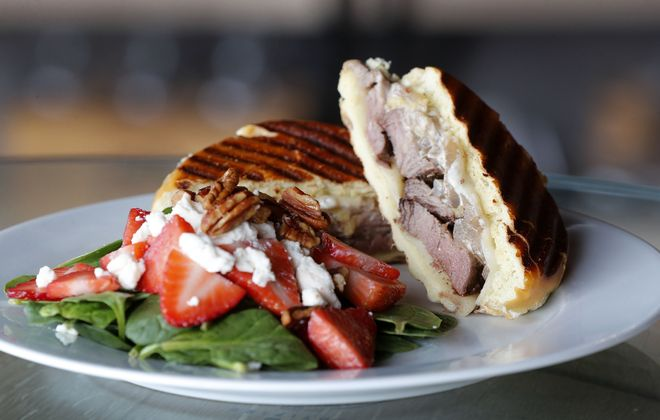 A beef tenderloin sandwich on brioche with caramelized onions and a horseradish cream sauce is served with a house strawberry spinach salad with honey goat cheese and candied pecans. (Mark Mulville/Buffalo News)