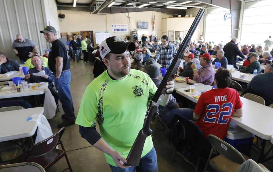 Firefighter Bryan Bader displays a Mossberg shotgun up for raffle during a gun raffle at the Jamison Road Volunteer Fire Company in Elma on Saturday. (Derek Gee/Buffalo News)