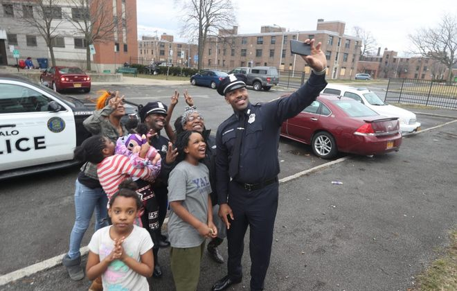 "Buffalo police officers Armonde ""Moe"" Bader, left, and Michael Norwood Jr. take a photo with residents of Commodore Perry housing complex after a video went viral earlier this year when they were caught on video singing an Ed Sheeran song at the Salsarita's downtown. (John Hickey/Buffalo News)"