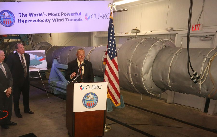 Sen. Charles Schumer next to a segment of a wind tunnel used in weapons development at CUBRC. (John Hickey/Buffalo News)