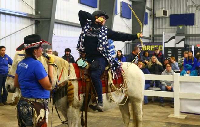 Diana Olds of the Chelee Warriors explains the sport of mounted archery with the help of Merissa Scalzo, the archer/rider, at WNY Equifest 2019, at the Agricultural Discovery Center Demonstration Area at Hamburg Fairgrounds on Saturday, March 23, 2019. (John Hickey/Buffalo News)