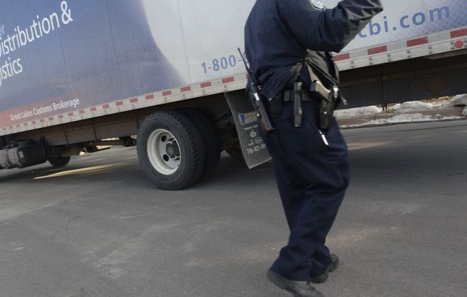 A U.S. Customs and Border Protection officer directs trucks into a search area. (Derek Gee/ News file photo)