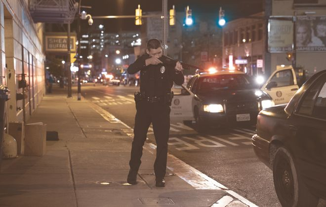 """Shea's Buffalo Theatre is seen in the background of this scene from the feature film """"Crown Vic."""" Pictured is  Luke Kleintank, starring as rookie police offer Nick Holland. (Photo by Phil Caruso)"""