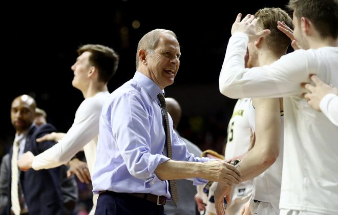 Michigan coach John Beilein congratulates players after win against Florida. (Jamie Squire/Getty Images)