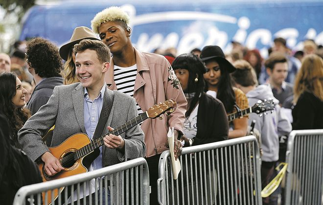 """John Cimino of Lewiston plays guitar as he waits in line in September to audition for """"American Idol"""" at Canalside. (Derek Gee/Buffalo News)"""