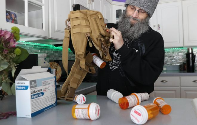 Jay Kuzara took five medications before his pain doctor cut his daily opioid prescription medication in half, after the federal Centers for Disease Control and prevention recommended that limit for new pain patients. Kuzara is now on 12 meds. (Sharon Cantillon/Buffalo News)