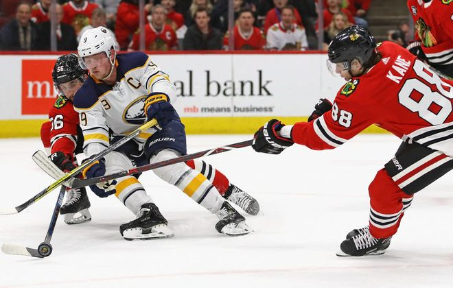Erik Gustafsson (56) and Patrick Kane combine to try to take the puck from Jack Eichel (Getty Images).