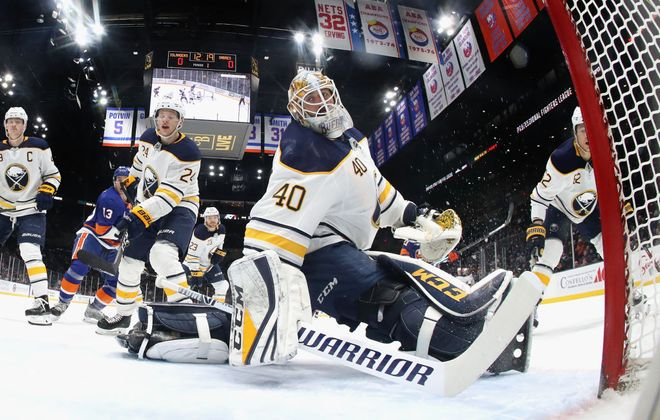Carter Hutton and Lawrence Pilut can't prevent Jordan Eberle's first-period goal that opened the scoring Saturday night. (Getty Images)