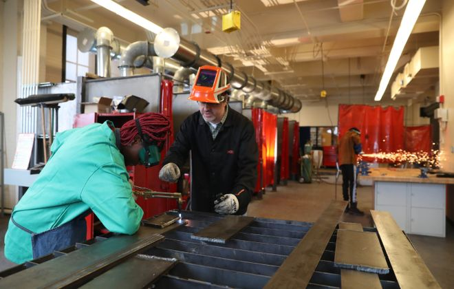 Burgard High School welding teacher James Ornello helps Janita Prim cut steel in the new welding shop. The school's advanced manufacturing program is helping redefine vocational education. (Sharon Cantillon/News file photo)