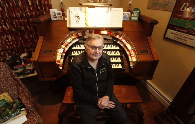 Ralph Bacha sits at the theater pipe organ installed in his Amherst house.  It is the second largest concert organ in New York State. (Mark Mulville/Buffalo News)