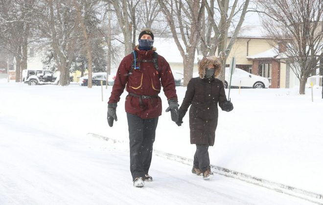 Austin Miller, left,  and his wife, Yukio, walk  home on Skinnersville Road on their daily 3.5 mile walk, in Amherst, on Sunday. (John Hickey/Buffalo News)