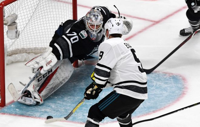 Jack Eichel works the puck against Metro goalie Braden Holtby. (Getty Images).