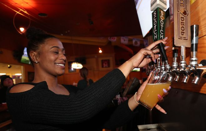 Tonawanda Bowling Center bartender Anjanett Edmonds pours a Guava Sutra Milkshake IPA Batch #2 by Three Heads Brewing out of Rochester. (Sharon Cantillon/Buffalo News)