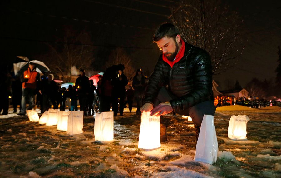 Phil Johnson tries to keep luminaries glowing at the site where Flight 3407 crashed during a vigil earlier this year. He lost his father-in-law Kevin Johnston. (Robert Kirkham/Buffalo News)