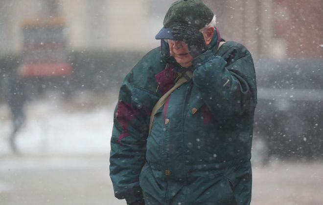 Tom Vaughan fights the intense wind at Niagara Square in front of City Hall on Wednesday. (Sharon Cantillon/Buffalo News)
