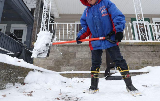 Joey Cordovez, 9, shovels out a neighbor's parking spot on Herkimer Street in Buffalo on Monday, Feb. 18, 2019. (Sharon Cantillon/Buffalo News)
