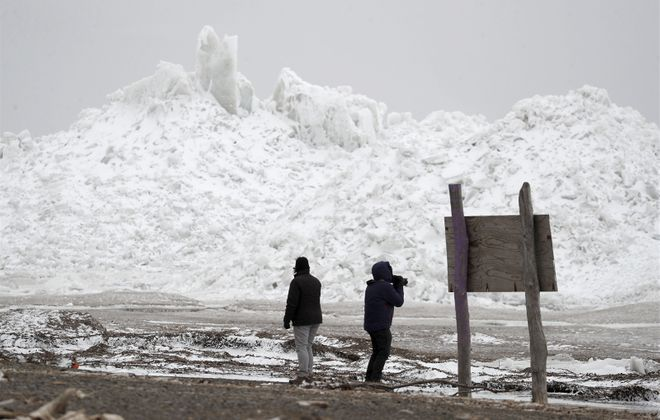 People explore the huge mounds of ice that were pushed toward Woodlawn Beach State Park in Hamburg on Monday, Feb. 25, 2019.(Mark Mulville/Buffalo News)