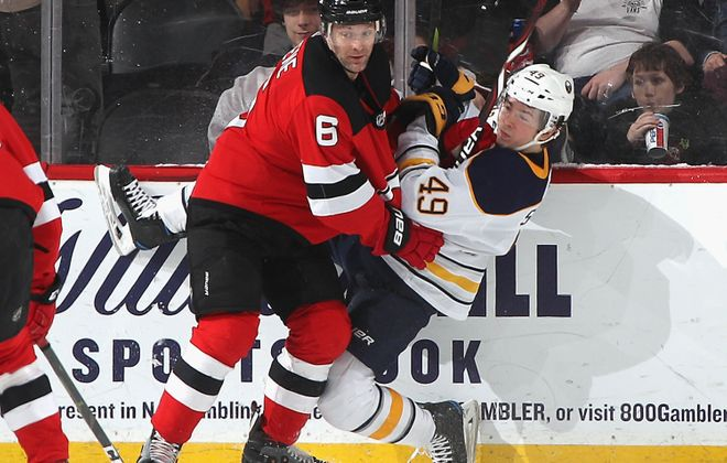 Devils defenseman Andy Greene checks Sabres winger C.J. Smith. (Getty Images)