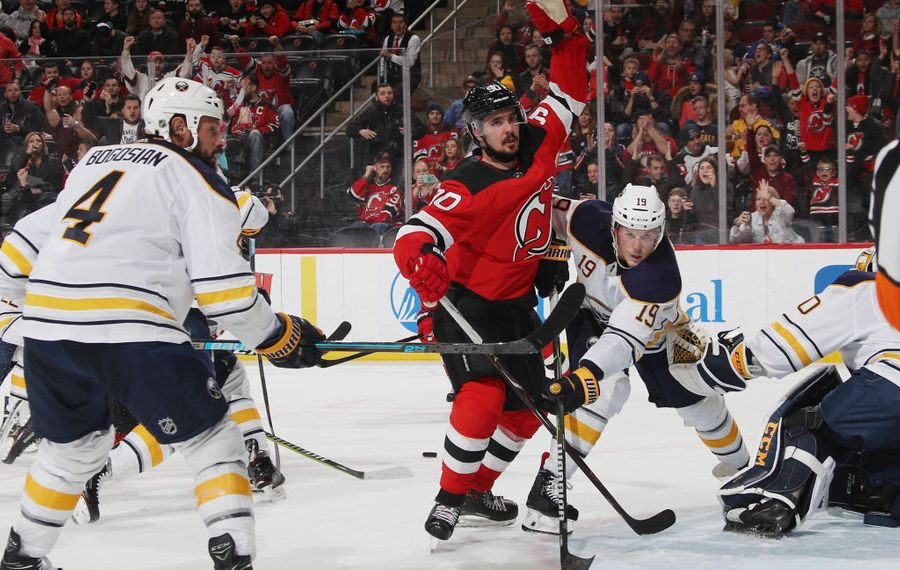 Zach Bogosian (4) and Jake McCabe (19) battle New Jersey's Marcus Johansson. (Getty Images)