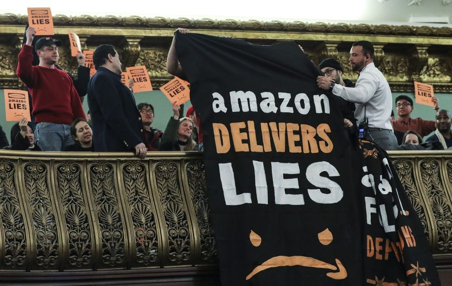 """Protestors unfurl anti-Amazon banners from the balcony of a hearing room during a New York City Council Finance Committee hearing titled """"Amazon HQ2 Stage 2: Does the Amazon Deal Deliver for New York City Residents?"""" at New York City Hall on Jan. 30.  (Getty Images)"""