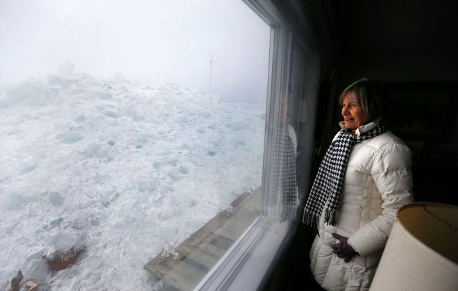 Fay Davis looks out to the ice mound that covers her patio at her home on Hoover Beach in Hamburg Monday afternoon. (Mark Mulville/Buffalo News)