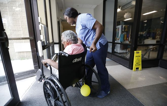 A resident of Ellicott Center for Rehabilitation and Nursing in Buffalo, gets help from staff through a doorway. (Derek Gee/News file photo)