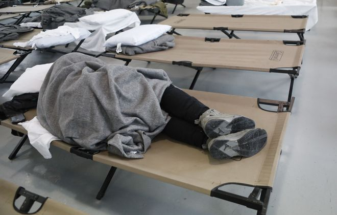 A man sleeps on a cot in the shelter at Holy Cross Church. (Derek Gee/Buffalo News)