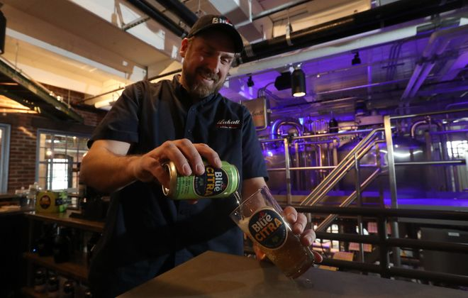 Ryan Brady, brewmaster at Labatt Brew House, pours a Labatt Blue Citra. Brady created the recipe for the new flagship Labatt USA brand – now available in 12-, 16- and 24-ounce cans – while he was an assistant brewer at Genesee Brewing Company in Rochester, which is owned by the same parent company. (Sharon Cantillon/Buffalo News)
