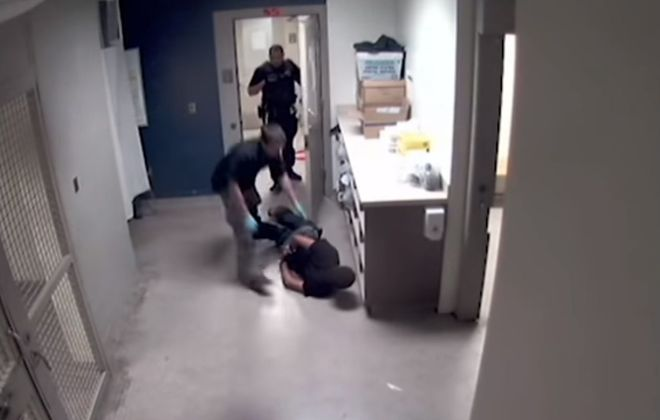 Buffalo Police holding cell attendant Matthew Jaskula drags handcuffed defendant Shaun Porter to a cell, causing him to suffer a facial injury that bled profusely. (Photo from City of Buffalo video)