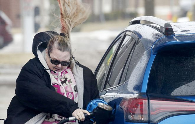 Kim Marie Kielbasa's ponytail whips in the wind Feb. 24 as she fills up her car at the Delta Sonic Gas Plaza on Walden Avenue in Cheektowaga. (Robert Kirkham/News file photo)