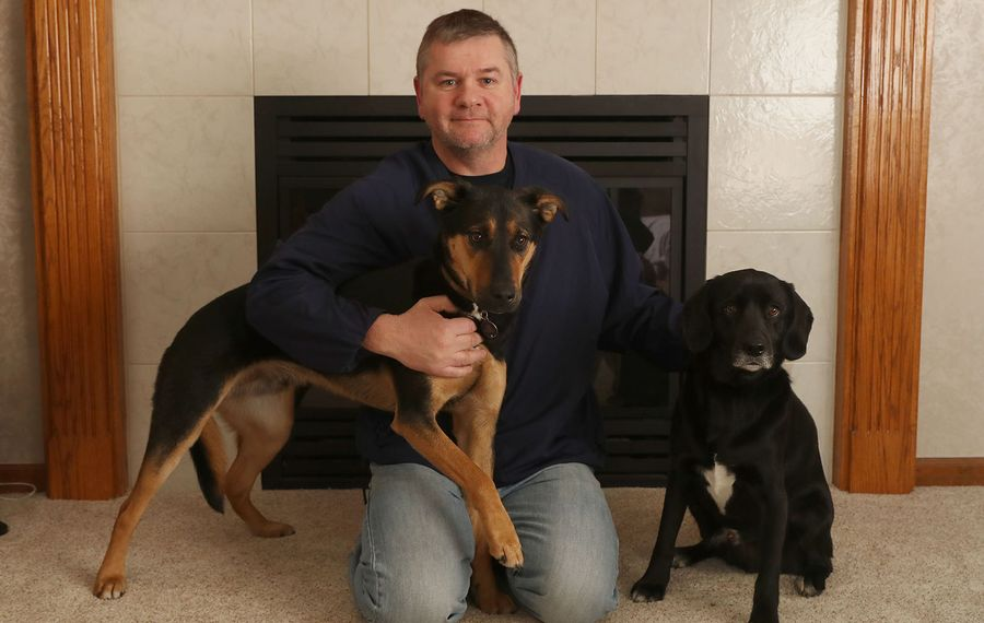 Don Chatten rescued a stranger's dog from the icy waters of the Tonawanda Creek on Thursday. He credits his two rescue dogs, Duke, left, and Milo for helping him find the dog who went missing in Ellicott Island Bark Park. (Sharon Cantillon/Buffalo News)