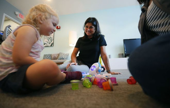 Deb Weber, director of Early Childhood Development Research at Fisher-Price, watches Melissa Buckenmeyer and her daughter Brynn play with some toys in the recently redesigned Fisher-Price Right-at-Home lab. (Mark Mulville/Buffalo News)